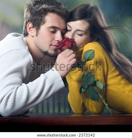 Young couple with rose, outdoors - stock photo