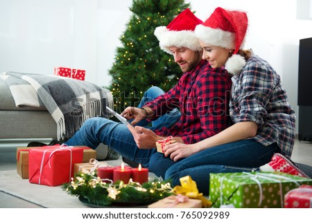 Young couple with Santa Claus hats shopping online Christmas gifts on a tablet