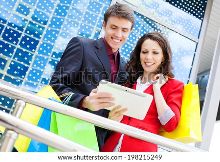 Young Couple with Shopping Bags looking at digital tablet - stock photo