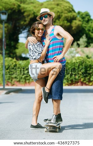 Young couple with skateboard in the street.