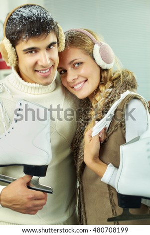 Young couple with skaters in snow looking at camera and smiling
