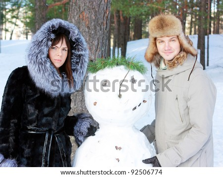 Young couple with snowman outdoors