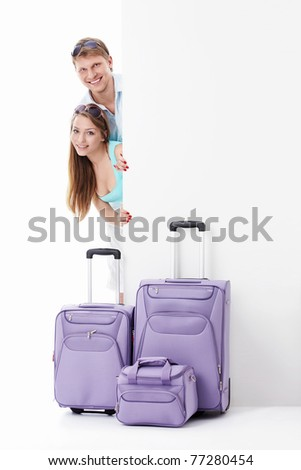 Young couple with suitcases and empty billboard on a white background - stock photo