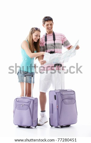Young couple with suitcases see map on a white background - stock photo