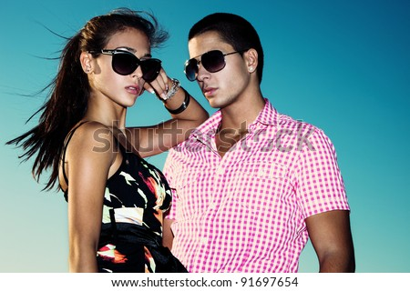 young couple with sunglasses outdoors shot against blue sky - stock photo
