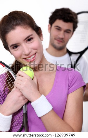 Young couple with tennis equipment - stock photo