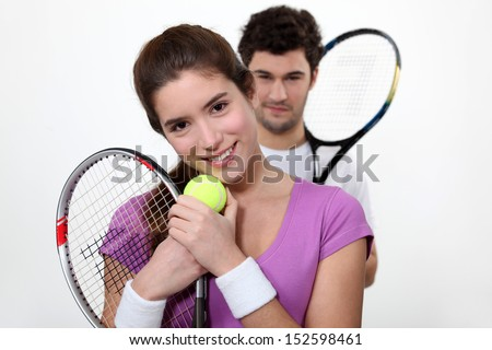 Young couple with tennis racquets - stock photo