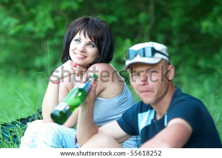 Young couple with the drinking man on the green field - stock photo