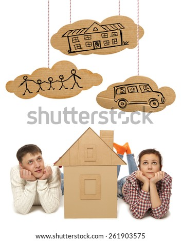 Young couple with the house of cardboard. Photo and hand-drawing elements combined - stock photo