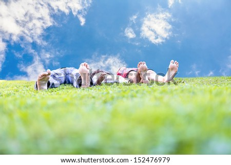 Young couple with their adopted african child lying in green grass. Concept of family happiness.