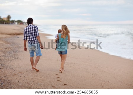 Young couple with their baby taking a stroll along the seashore - stock photo