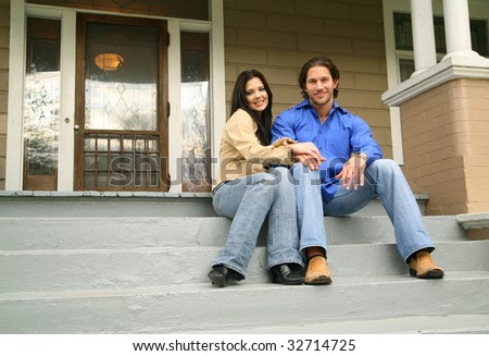 young couple with their new house. smiling and looking to camera