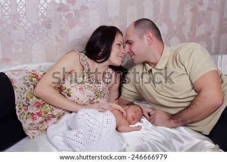 Young couple with their newborn baby - stock photo