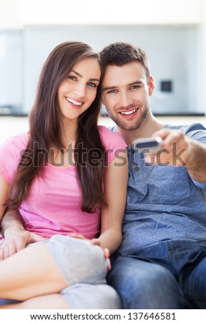 Young couple with TV remote - stock photo