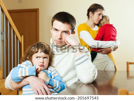 Young couple with two children in quarrel - stock photo