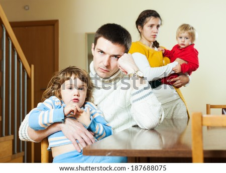 Young couple with two small children after quarrel at home - stock photo