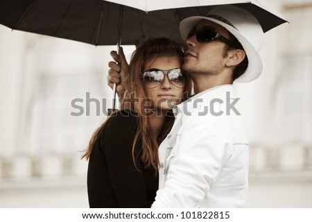 Young couple with umbrella - stock photo