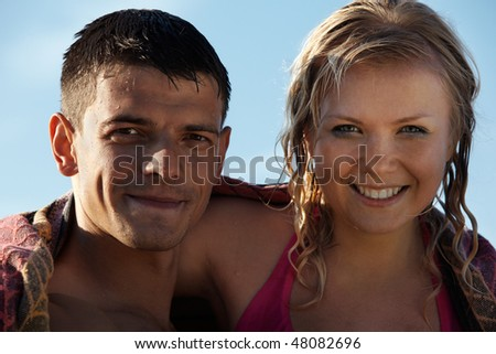 young couple with wet hair posing in beach outfit