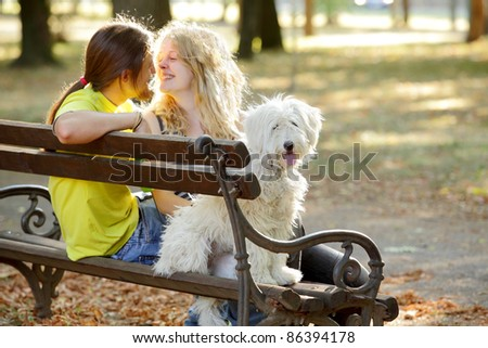 Young couple with white dog at bench