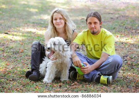 Young couple with white dog at ground