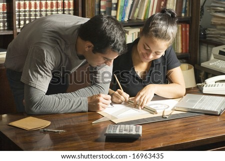 Young couple working at desk with a protractor, laptop computer, and a map - stock photo