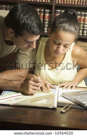 Young couple working at desk with a protractor, laptop computer, and a map. Vertically framed shot. - stock photo