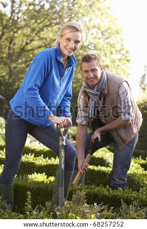 Young couple working in garden - stock photo