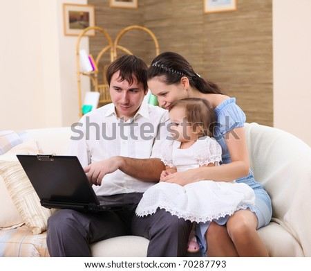 young couple working on a laptop computer sitting on the sofa at home
