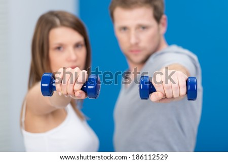 Young couple working out together with dumbbells holding them extended towards the camera as they stand side by side with focus to the weights - stock photo