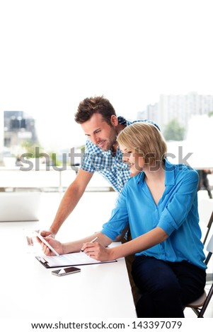 Young couple working together on digital tablet in the office. Teamwork concepts. - stock photo