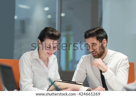 Young couple working together on tablet  computer. Teamwork, help, support concept.  Business group  at modern startup office meeting room interior working online on project plans. - stock photo