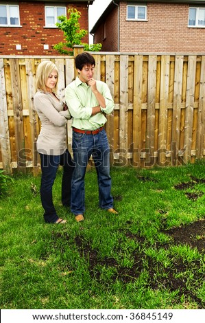 Young couple worried about growing lawn in backyard of new home - stock photo