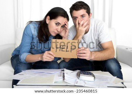young couple worried need help in stress at home couch accounting debt bills bank papers expenses and payments feeling desperate in bad financial situation - stock photo