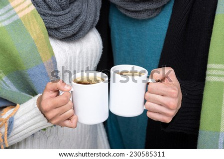 Young couple wrapped a warm blanket, are holding hot tea. - stock photo