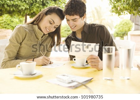 Young couple writing postcards in a coffee shop while on vacations.