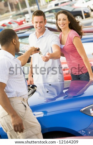Young coupled collecting new car from salesman - stock photo