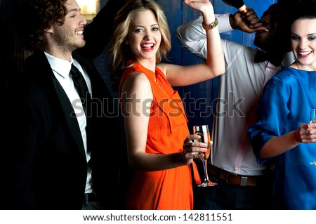 Young couples drinking and dancing in a club. - stock photo