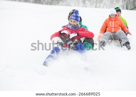 Young couples enjoying sled ride on snow covered slope - stock photo