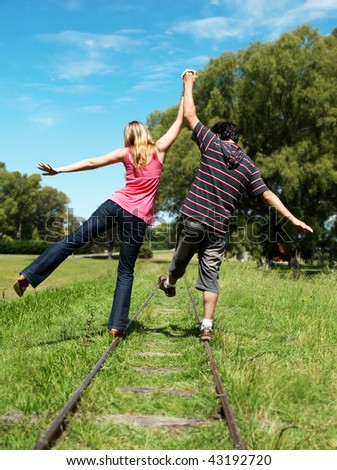 young couples going along a railroad line - stock photo