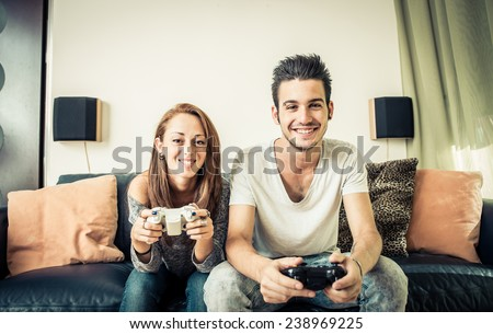 young couples playing video games on the living room. concept about home entertainment - stock photo