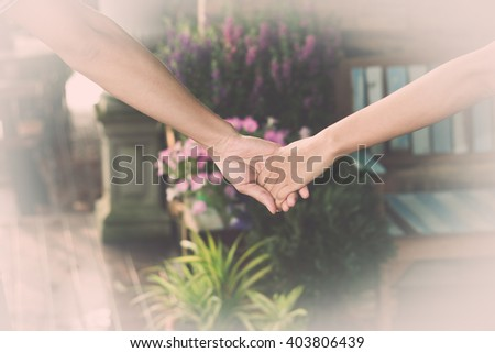 Young couples walk hand in hand. - stock photo
