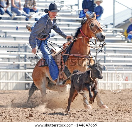 Young cowboy dismounting his horse after roping a calf during a rodeo. - stock photo