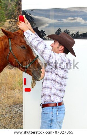 Young cowboy grooming his horse at the trailor - stock photo