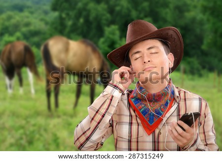 Young cowboy in earphones is listening country music with smart phone. He is wearing brown cowboy hat, plaid shirt and colored bandana neckerchief - stock photo