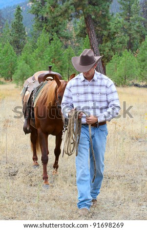 Young cowboy leading his horse through the field - stock photo