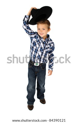 Young cowboy lifting his hat to greet someone - stock photo