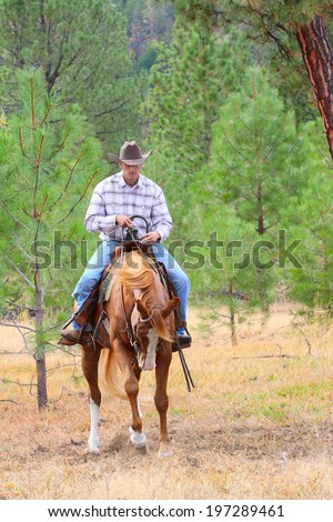 Young cowboy riding his horse in the field  - stock photo