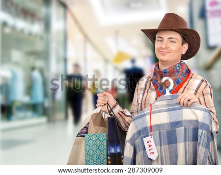 Young cowboy shopping in the mall with shopping bags in left hand. In right hand, he holds blue and white plaid shirt on hangers with tag sale - stock photo