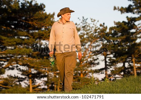 Young cowboy sitting in the field - stock photo