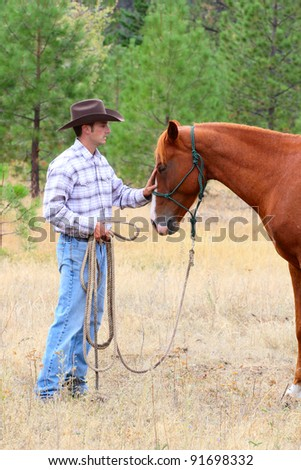 Young cowboy touching his horse on his nose - stock photo